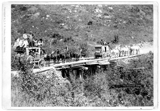 1889: Two stagecoaches cross a bridge near Deadwood, South Dakota.