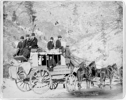 The Deadwood Coach: 1889: Formally dressed men ride on the Deadwood, South Dakota, coach. The photograph was taken in 1889 by John C. H. Grabill.