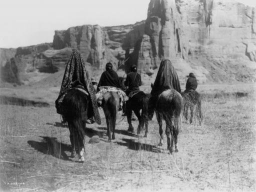 March through Tesacod Canyon: Navajo Indians on horseback making their way over the dry, grassy floor of Tesacod Canyon, Arizona. Photograph by Edward S. Curtis, 1905.