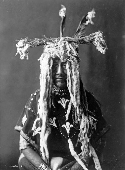 Piegan man wearing a headdress: Piegan man wearing a headdress made of ermine tails, feathers, and bunches of grass. Photograph by Edward S. Curtis, c 1910.