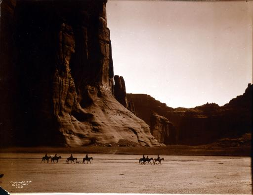 Canon de Chelly: c1904: Seven Navajo riders on horseback and a dog trek in front of the Canon de Chelly cliffs in Arizona. Photograph taken c1904 by Edward S. Curtis.