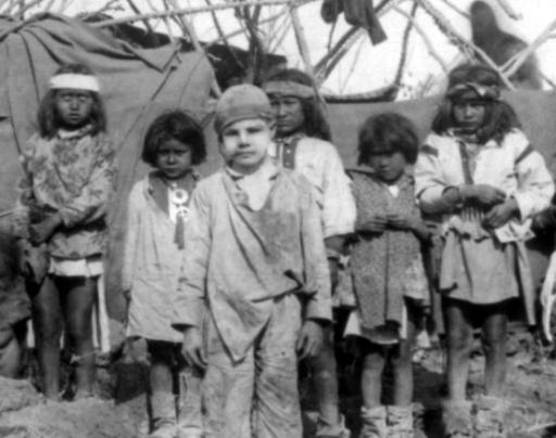 Captive White Boy: The captive white boy, Santiago McKinn, poses with a group of children in Geronimo's Camp. This photo is a detail from a larger image. Behind him is a partially constructed tent. The photo by Camillus Sidney Fly was taken in 1886 shortly before Geronimo's