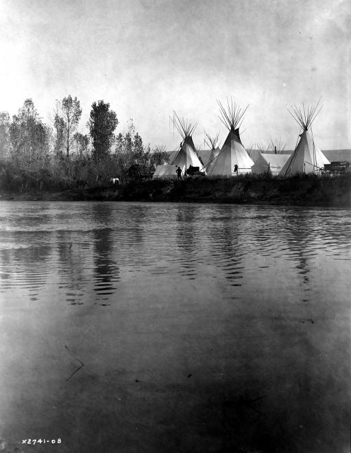 Crow Encampment: c1908: A Crow Indian encampment with tipis, tents, wagons, horses and men as seen from the distant shore of the river. Photograph was taken by Edward s. Curtis, c1908.