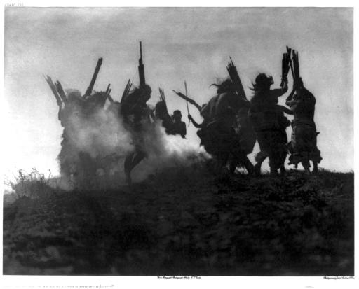 "Dancing to restore an eclipsed moon: ""Several Kwakiutl people dancing in a circle around a smoking fire, in an effort to cause a sky creature, which they believe swallowed the moon, to sneeze thereby disgorging it."" The photo was taken in British Columbia in 1914 by Edward S. Curtis."