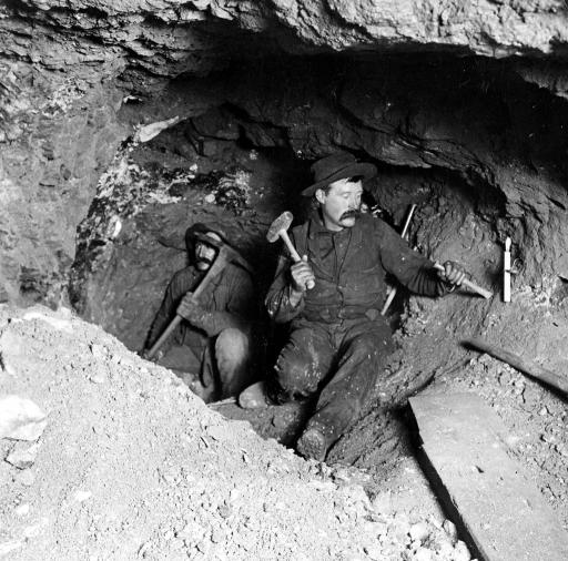 Working in a gold mine: Miners work taking out ore in a gold mine in Eagle River Canyon, Colorado. Note the candle in the foreground.