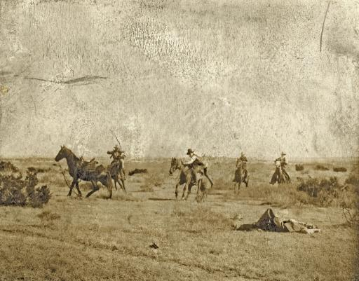 Heavily Thrown: Photograph shows a cowboy on the ground after being thrown from his mount and other cowboys on horseback coming to his aid, on the Turkey Track Ranch in Texas. Photographed by Erwin Evans Smith, c1906.