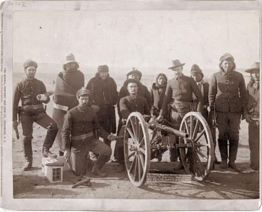 Near Wounded Knee: Seven Lakota scouts and four uniformed Euro-Americans posed behind an artillery piece or Hotchkiss gun, probably in the Pine Ridge Reservation near Wounded Knee, South Dakota. Photograph taken by John C. H. Grabill, 1891.